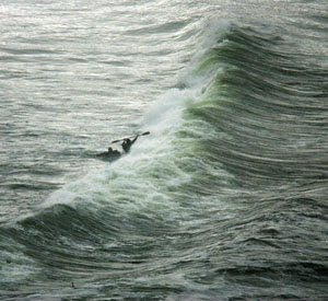 "John Weed paddles out against surf breaking on the Klamath bar."" Photo by Michael Maloney, SF Chronicle"