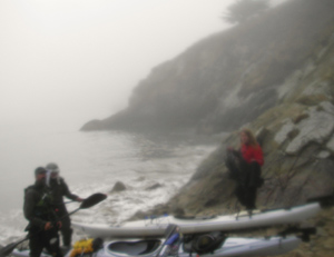 Paddlers in the mist – we find a place to land and camp at the foot of a wharf. Photo by John Weed.