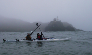 McHugh and Barnes give a paddle salute to the Point Bonita light. Photo by John Weed.