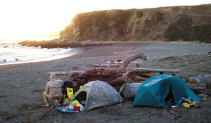 Our camp on the beach in the cove at Fort Ross. Note the screen of stacked logs to protect our tents from wind gusts.