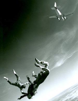 Jumpmasters train McHugh in freefall.