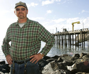 Harbormaster Mitch McFarland stands near the foot of his wharf at Point Arena.