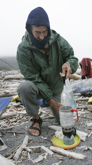 John Weed kneels in camp to spark up his stove. Photo by Michael Maloney, SF Chronicle.